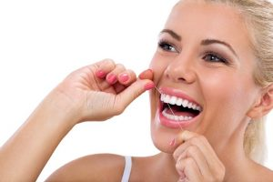 Woman with object stuck between teeth flossing